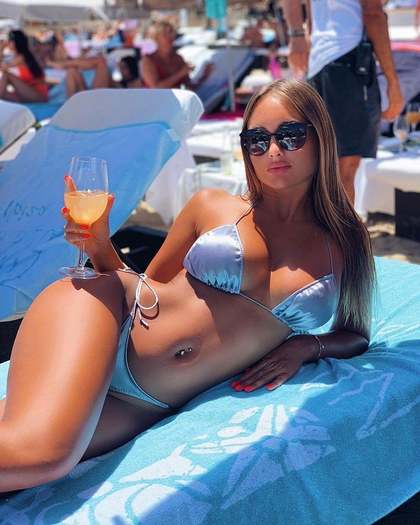 Шикарная туристка позирует на пляже в купальнике