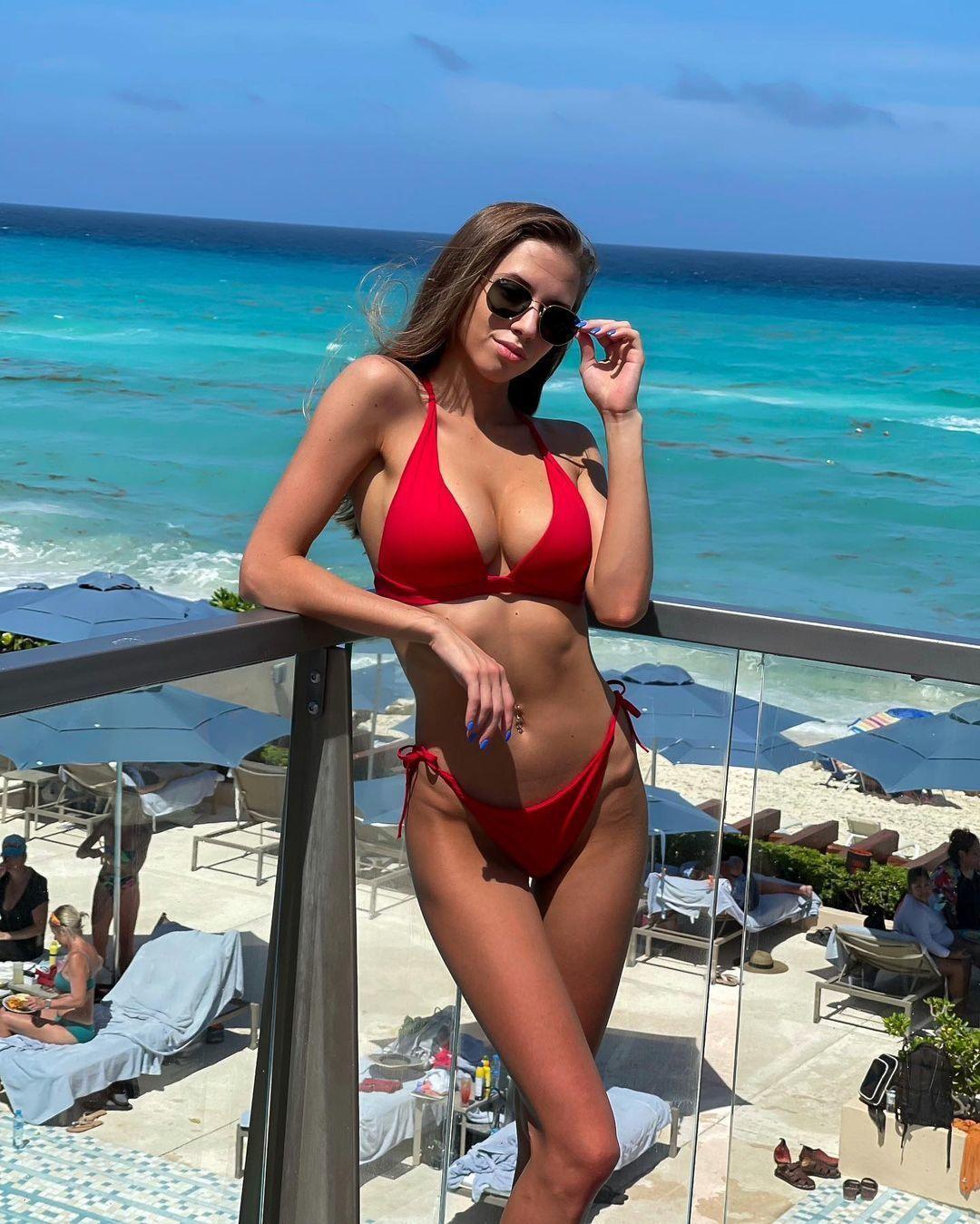 Стройная туристка в сексуальном красном купальнике на отдыхе