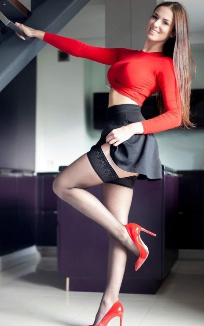 Няшка в короткой юбке и чулках сексуально позирует