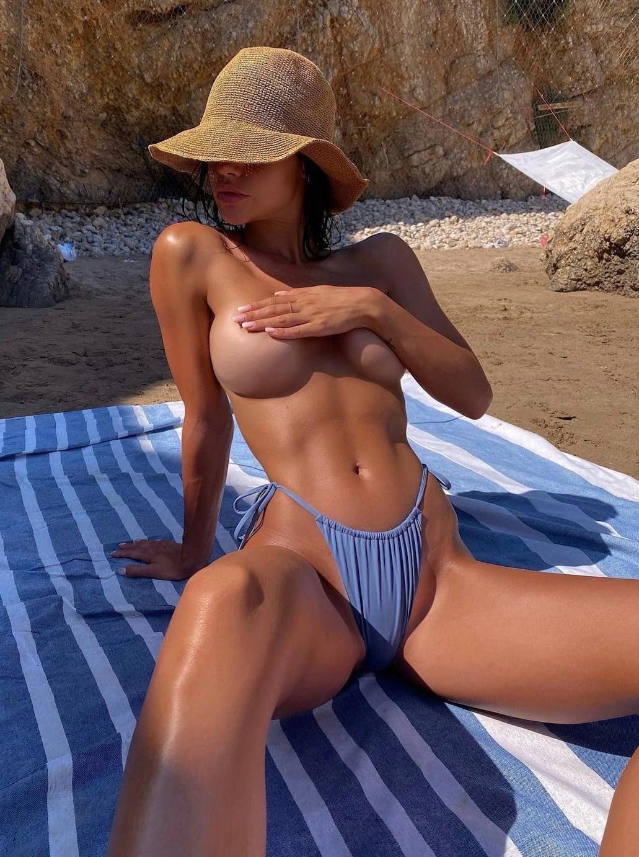 Молодуха в панамке загорает на пляже топлес