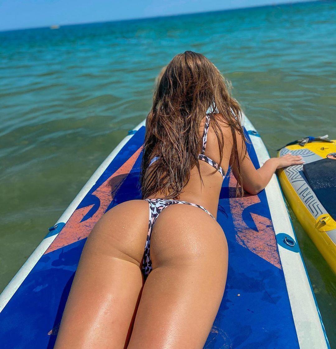 Молодая загорелая попочка катается на доске от сёрфинга